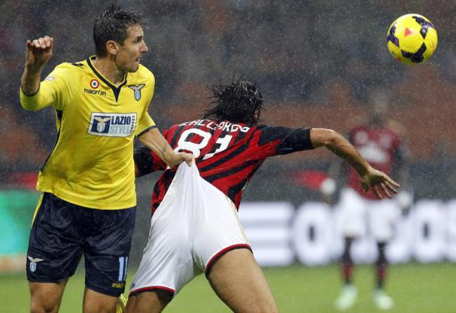 AC Milan's Cristian Zaccardo fights for the ball with Lazio's Miroslav Klose during their Italian Serie A soccer match at San Siro stadium in Milan